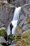 tourist standing in the front of a waterfall - stock photo