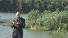 Businessman outdoor wild lake and nature background wired people anywhere, phone Stock Footage