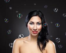 Young beautiful woman surrounded by bubbles Stock Photos