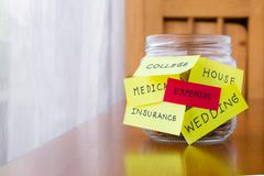 expenses and orther tags on savings money jar - stock photo