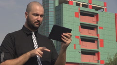 Businessman use smart gadget outside corporation building tablet working, stress - stock footage