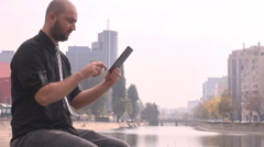 Stylish man wearing black shirt and tie outdoor, business communication, tablet - stock footage