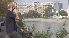 Young student 20s outdoors talk on smartphone, city lifestyle, alive town view Stock Footage