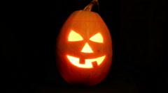 Halloween pumpkin jack-o-lantern candle lit, isolated on black - stock footage