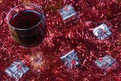 Glass of red wine with decorations and small gifts Stock Photos