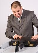businessman cut case on an circular saw - stock photo