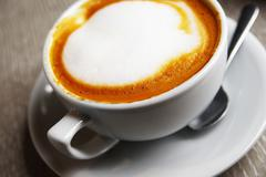 closeup of a cup of frothy cappuccino - stock photo