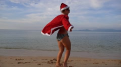 Woman on the Beach in Santa Claus Suit. Slow Motion. Stock Footage