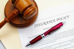 insurance policy and legal gavel with pen - stock photo