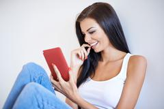 Woman smiling as she reads an sms - stock photo
