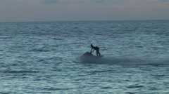 Man riding a jet ski in the ocean at sunset. Stock Footage