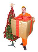 Serviceman carries a large package beside the Christmas tree Stock Photos