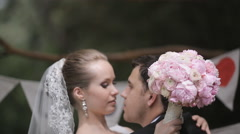 Newlyweds kissing in a nicely decorated with letters park Stock Footage