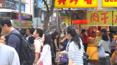 Pan left crowded downtown Hong Kong tourist people cross busy road commercial  - stock footage