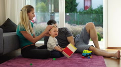 Young family relaxing in living room Stock Footage