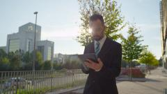 SLOW MOTION: Worried businessman checking news on digital tablet outdoors - stock footage