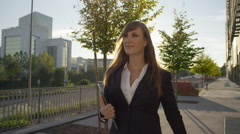 CLOSE UP: Cheerful business woman walking to work in sunny morning - stock footage