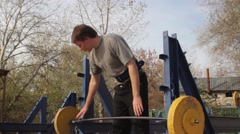 Guy picks up a heavy barbell in street gym. The autumn. Stock Footage