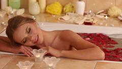 Woman relaxing in bath with rose petal. Stock Footage