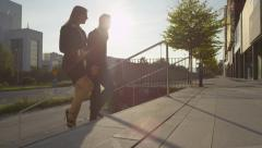 SLOW MOTION: Business couple going to work on sunny morning - stock footage