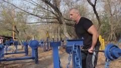 The man raises the bar in the Park. Body building. Stock Footage