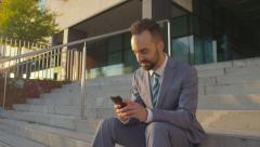CLOSE UP: Happy businessman browsing the internet on his smartphone - stock footage