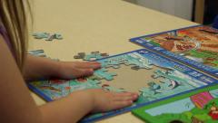 Preschooler flattening out puzzle Stock Footage