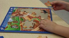 Preschooler having trouble with elusive piece - stock footage
