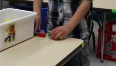 Preschooler creating a long chain using blocks - stock footage