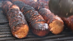 Cooking cut polish sausages on the fire pit's grill Stock Footage