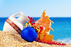 Antique vase, christmas baubles, gift box and seashell on the sand Stock Photos