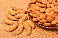 peeled almonds on the ceramic saucer and in the nutshell - stock photo