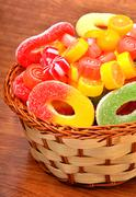bright sweets, lollipops, jellies in the wicker basket - stock photo