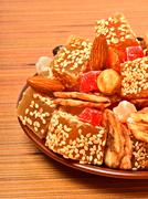 turkish sweet delights with sesame, dried bananas, candied fruits on the plat - stock photo