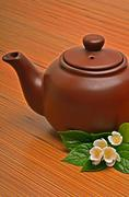 Clay brown teapot and jasmine flower on the wood Stock Photos