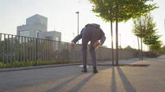 Wind blows businessmans papers and he rips pants catching them Stock Footage