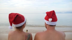 Happy Couple in Santa Caps Toasting with Beer on the Beach. Stock Footage