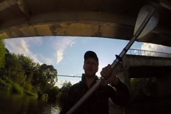 Young man tourist paddling boat under bridge, fishing, slow-mo, click for HD Stock Footage