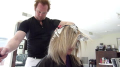 Hair highlighting at Salon - Low angle applying dye Stock Footage