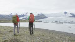Travel people hiking adventure in Iceland nature - Hikers walking by glacier Stock Footage