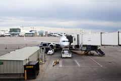 Commercial jet plane at jetway loading luggage Stock Photos