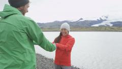 Happy couple having fun laughing dancing on Iceland - fun by glacial lagoon Stock Footage