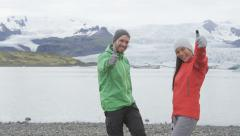 Thumbs up happy people hiking on Iceland hike -  couple hiking by glacier Stock Footage