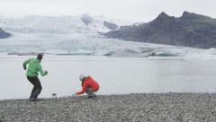 Iceland people skipping stones in glacial lagoon - people on hiking adventure Stock Footage