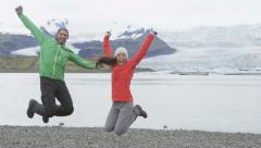 Jumping happy people celebrating on Iceland hike - Cheering elated hikers jump Stock Footage