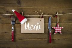 christmas menu card for restaurants with knife and fork on wooden background. - stock photo