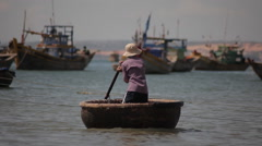 Fisherman sailing in traditional Vietnamese round boat with one oar. - stock footage