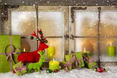 festive christmas window decoration in green and red with presents and candle - stock photo