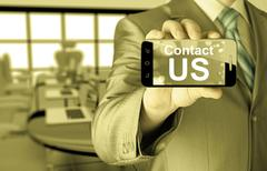 business man hand holding smartphone with the message contact us - stock illustration