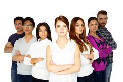 Casual group of young serious people looking at the camera on white backgroun Stock Photos